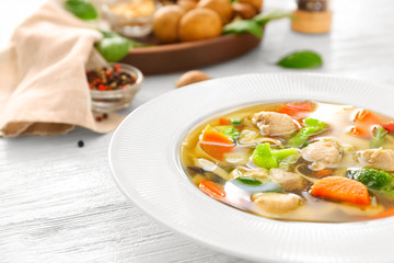Plate with delicious turkey soup on wooden background, close up