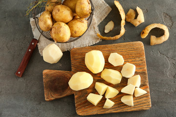 Composition with raw peeled potatoes on table