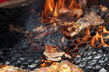 Close up of delicious whole lamb chop meat pieces on a grill under flames