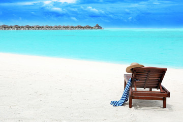 Wooden sun lounger with beach accessories at sea resort