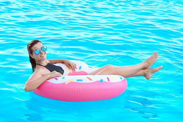 Beautiful young girl with inflatable donut in blue swimming pool