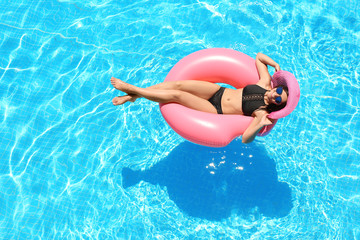Beautiful young woman with inflatable ring relaxing in blue swimming pool