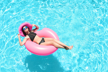 Beautiful young woman with inflatable ring in blue swimming pool