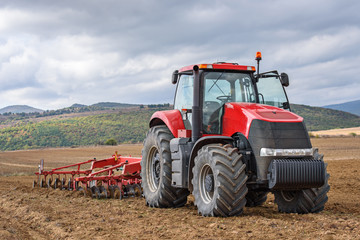 Fototapete - Farmer in tractor preparing farmland for seedbed.