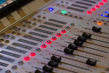 The buttons, sliders, lights, buttons and controls of a sound engineer or DJ's mixing desk or control console.