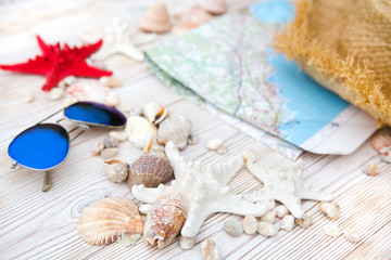 summer holiday background with straw hat, map and seashells on wooden background.