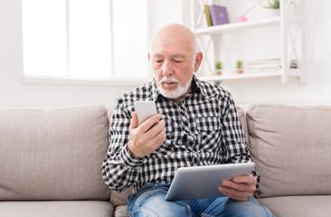 Senior man using phone and tablet