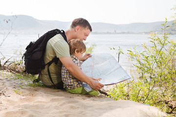 Father and son looking with map relaxing outdoor on background summer vacations and Lifestyle hiking concept.