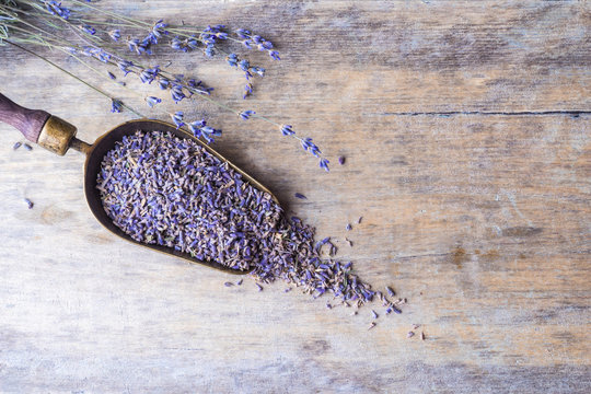 Lavender flowers in an antique scoop on wooden background. Top view.
