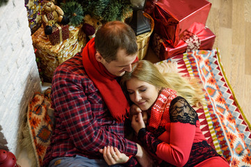Young couple cuddling and kissing near christmas tree. Merry Christmas and Happy New Year!