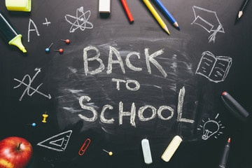 Back to school. School supplies on the chalkboard background, education concept