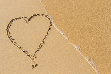 Heart drawn on a sand of beach with the wave of the sea in the morning with place for your text. Summer holiday concept. Romantic love background. Valentine's Day theme. Top view. Copy space.