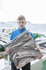 A young fisherman holds a block of frozen cod