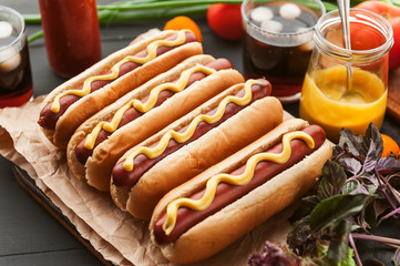 American hot dog with ingredients on a dark wooden background