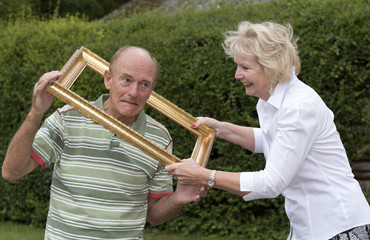 Elderly couple playing with a gold picture frame