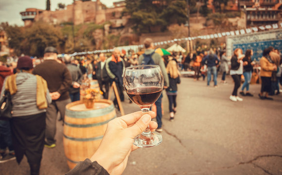 Wine drinkers on the city festival and crowd of people around.