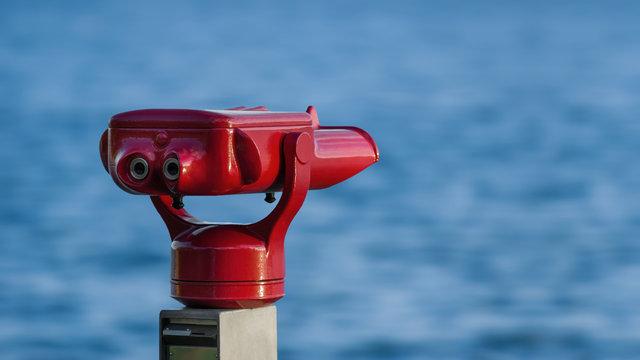 Ein rotes Fernrohr am Ufer des Bodensees bei Überlingen mit Blick auf das Wasser, die Berge und den bewölkten bunten Himmel