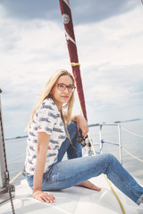 Slim blonde in jeans sitting on nose of white yacht