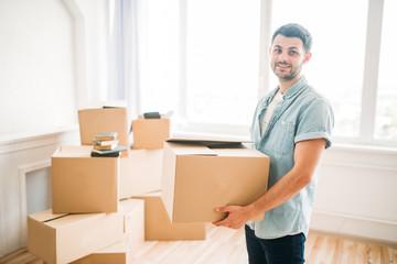 Man holds carton box in hands, housewarming