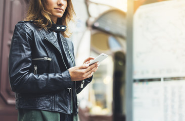Fotomurales - Girl in leather jacket holding smart phone on background map light box in city, hipster using in female hands and texting mobile, glitter street lifestyle, tourist planing route in summer concept