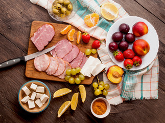 A set of meat delicacies, cheese and fruits on a dark, wooden background. Top view, banner for a cafe.