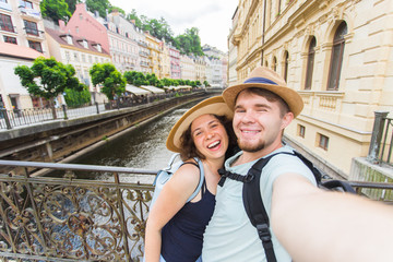 Happy couple, attractive woman and man walking in city and enjoying romance. Lovers making selfie and smiling. Tourists having fun together. Prague , Czech Republic