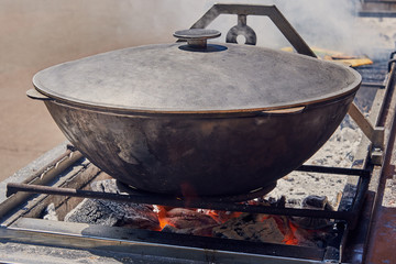 Cooking food in the vat over the coals