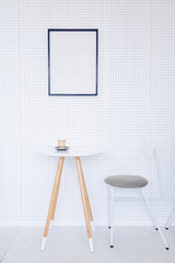 Corner of a kitchen with a table, gray chairs and a poster hanging on a light gray wall.