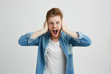 Angry rage young man with beard shouting screaming closing ears over white background.
