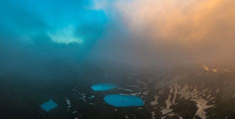 Azgara mountain lakes in last beams of sun. Top view through clouds.  Caucasus mountains.