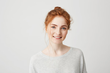 Portrait of happy tender ginger girl with blue eyes and freckles looking at camera smiling over white background.