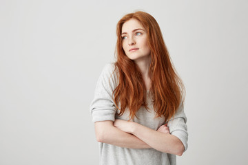 Portrait of beautiful ginger girl with freckles looking in side with crossed arms over white background.
