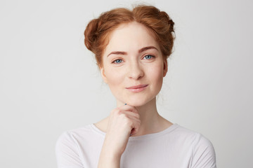 Portrait of young pretty girl with red hair smiling looking at camera touching chin over white background.