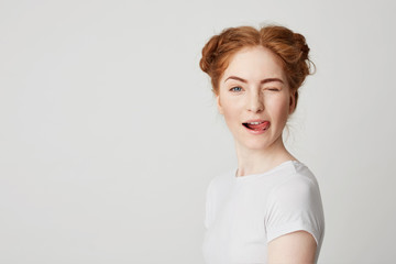 Portrait of beautiful redhead girl smiling showing tongue winking looking at camera over white background.