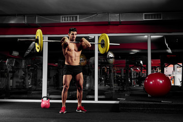 Young muscular man is doing squats with a barbell in the gym.