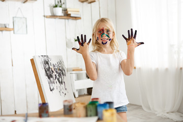 Joyful female caucasian kid demonstrating her hands in black paint, standing behind easle with her picture. Little blonde creative and talented girl with her face in paint wearing casual cloth