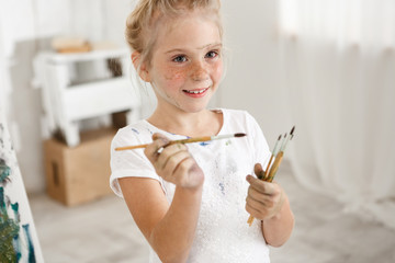 Close-up portrait of blonde cute European little girl with paint on her freckled face and hair bun smiling with all her teeth holding a bunch of brushes in her hands. Cheerful girl messed up her white