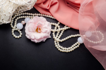 Abstract beauty decoration background with flower, pearl necklace and pink fabric on black table.