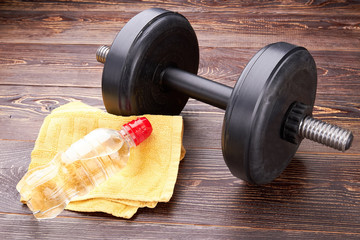 Dumbbell, towel, bottle close up. Concept of gym and sport activity.