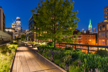 High Line promenade at twilight with city lights and illuminated skyscrapers. Chelsea, Manhattan, New York City