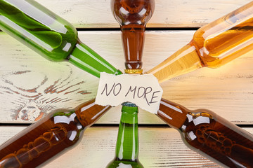 No more to alcohol drinking, concept. Paper message on collection of glass bottles.