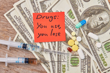 Amount of money, narcotics, message close up. Drugs: you use, you lose.