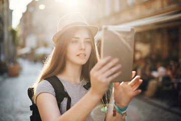 Female tourist using a tablet to search for interesting locations or find her way or just chatting with friends via video. Travel concept.