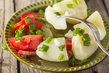 Boiled potato with tomatoes and green onions