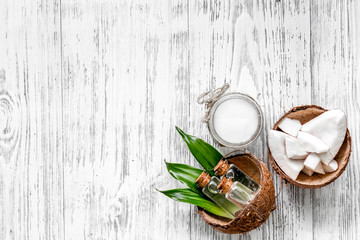 Organic cosmetics with coconut. Coconut oil and lotion on wooden background top view copyspace
