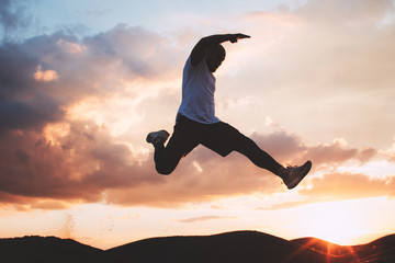 Strong and brave athlete jumps over a ditch. Silhouette of a man at the moment of a jump