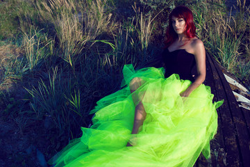 Portrait of young beautiful red haired woman in black corset and long tail green veiling skirt lying on the shabby upside down wooden boat in the middle of the field with dry grass. Copy-space