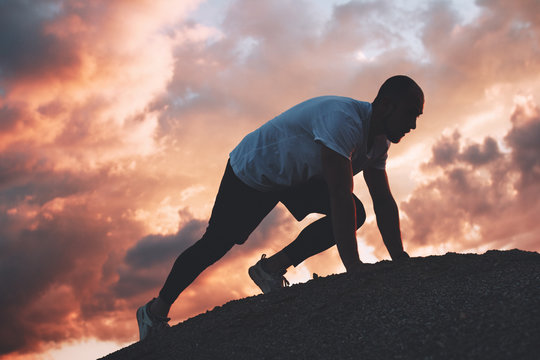Man in start position ready for sprint. Outdoors workout. Fast running exercise. Sunset