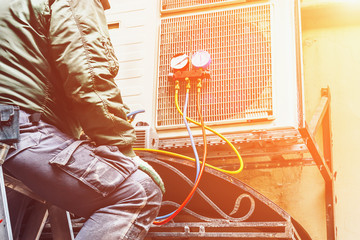 The worker repairs or prevents the air conditioner on the wall, Air Conditioning Repair concept