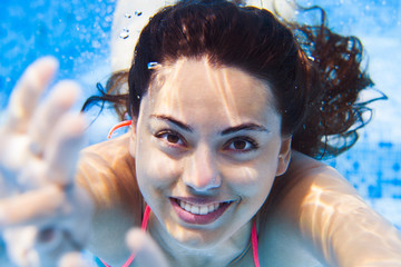 Portrait Young smiling woman swimming undewater in the swimming pool